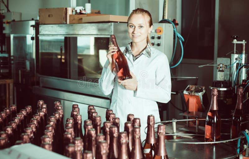 Kvinna som rymmer nyligen producerade flaskor av vin arkivbilder