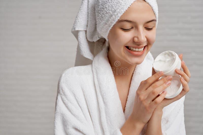 Kvinna som rymmer och visar asken med fuktighetsbevarande hudkräm för framsida arkivfoton