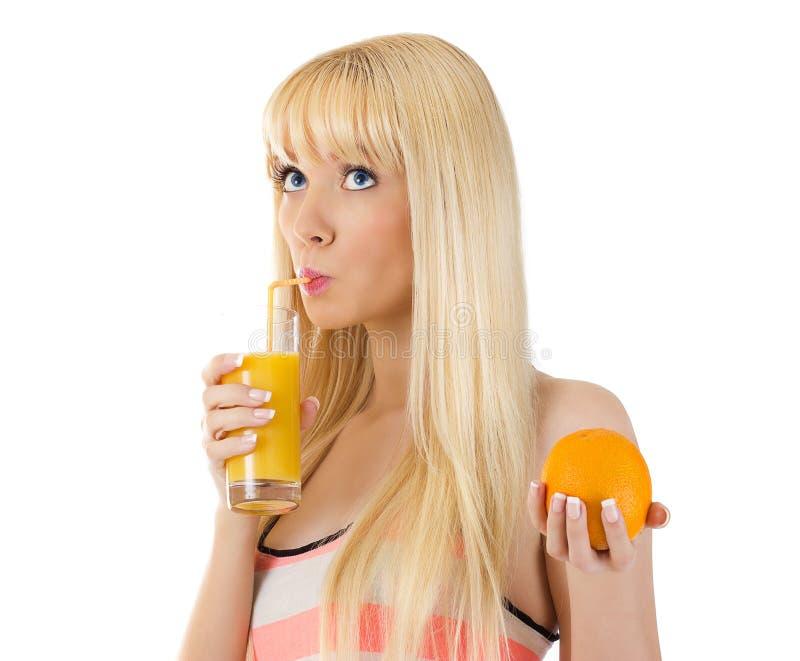 Kvinna som rymmer orangen, medan läppja exponeringsglas av fruktsaft arkivfoton