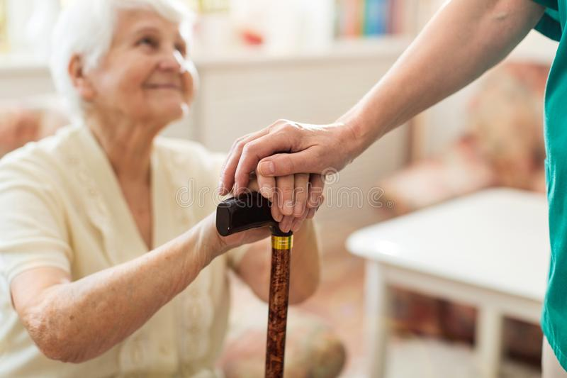 Kvinna som rymmer pension?rs h?nder som lutar p? att g? rottingen arkivbild