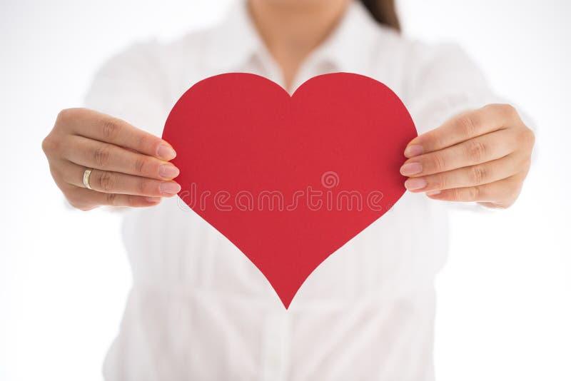 Kvinna som rymmer röd hjärta i hans händer, closeup royaltyfri foto