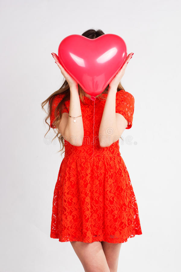 Kvinna som rymmer röda hjärtaballonger arkivbilder
