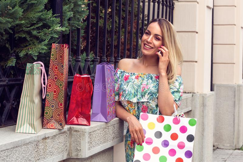 Kvinna som rymmer shoppingpåsar, använder en smart telefon och ler, medan stå utomhus fotografering för bildbyråer