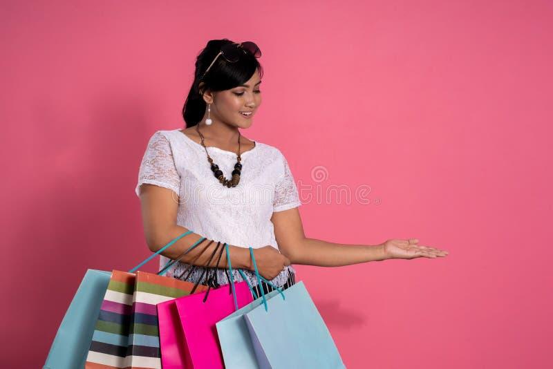 Kvinna som rymmer shoppingpåsar, och hand som framlägger gest royaltyfri fotografi