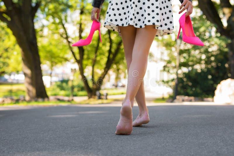 Kvinna som rymmer skor för hög häl i händer och går med kal fot royaltyfri fotografi