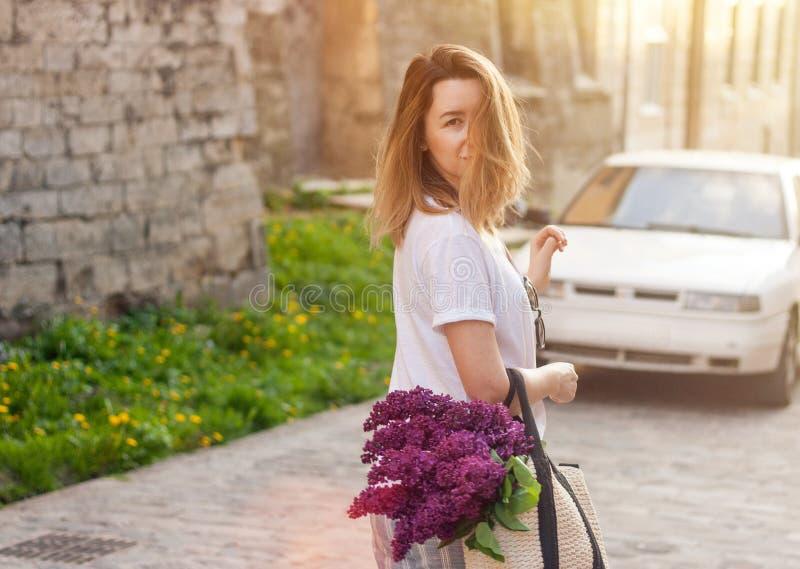 Kvinna som rymmer sugrörpåsen med den livliga gruppen av lila blommor som går ner gatan royaltyfri fotografi