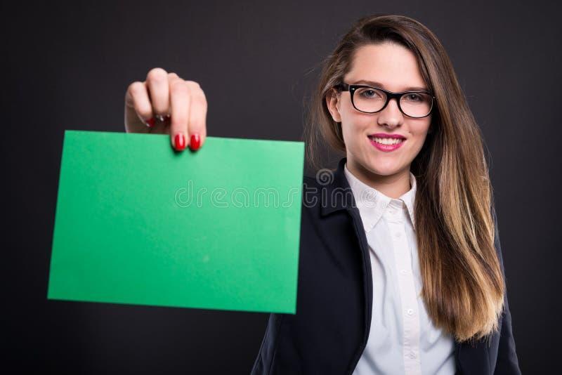 Kvinna som rymmer tomt papper med copyspace fotografering för bildbyråer
