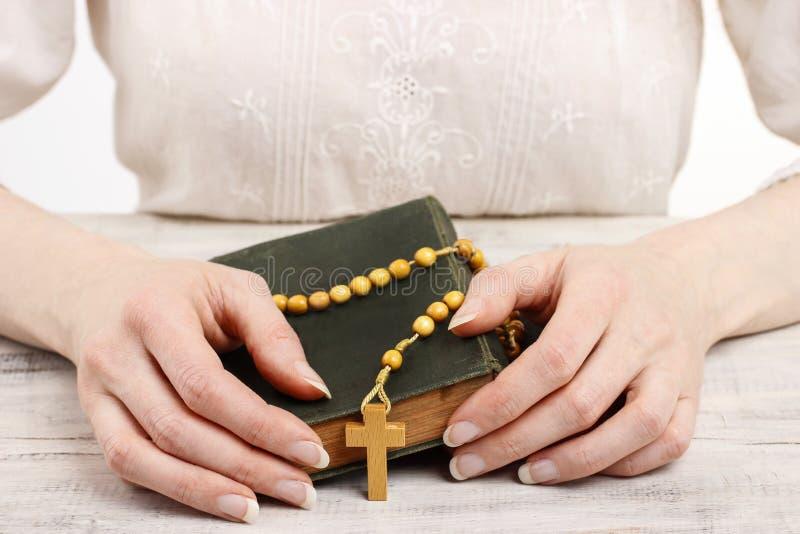 Kvinna som rymmer träradbandet och den heliga bibeln. royaltyfri foto