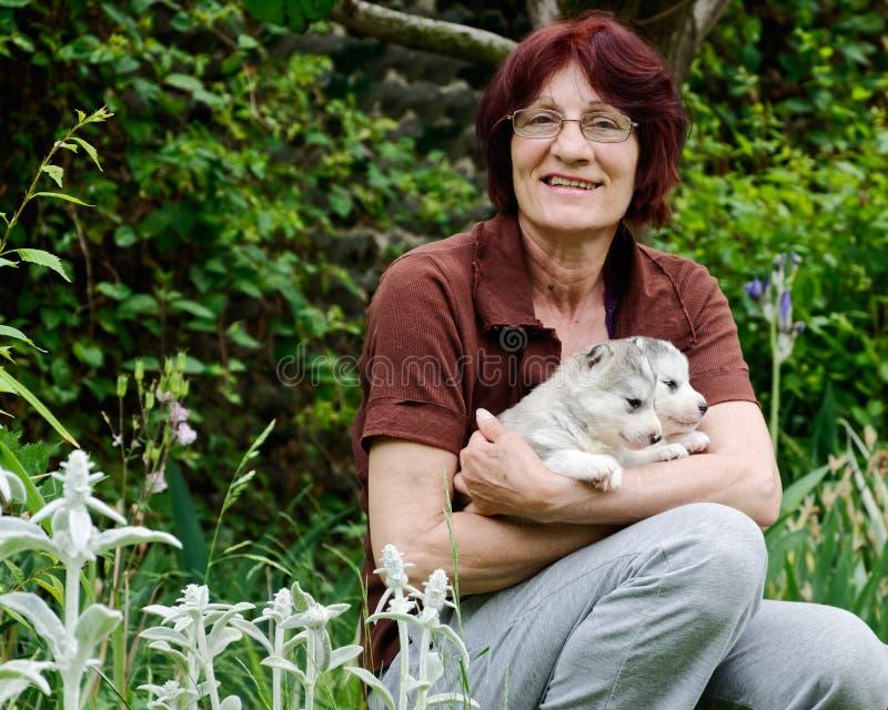 Kvinna som rymmer två Siberian Husky Puppies fotografering för bildbyråer