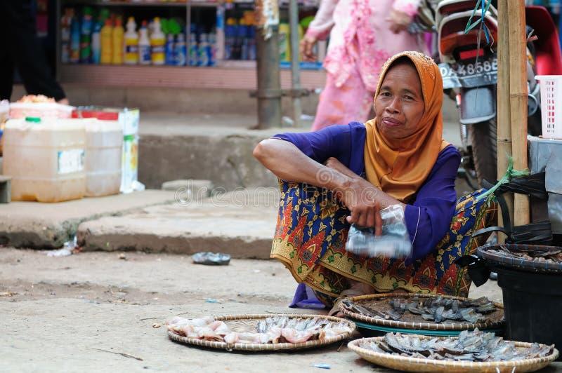 Kvinna som säljer den torkade fisken i Indonesien arkivfoto