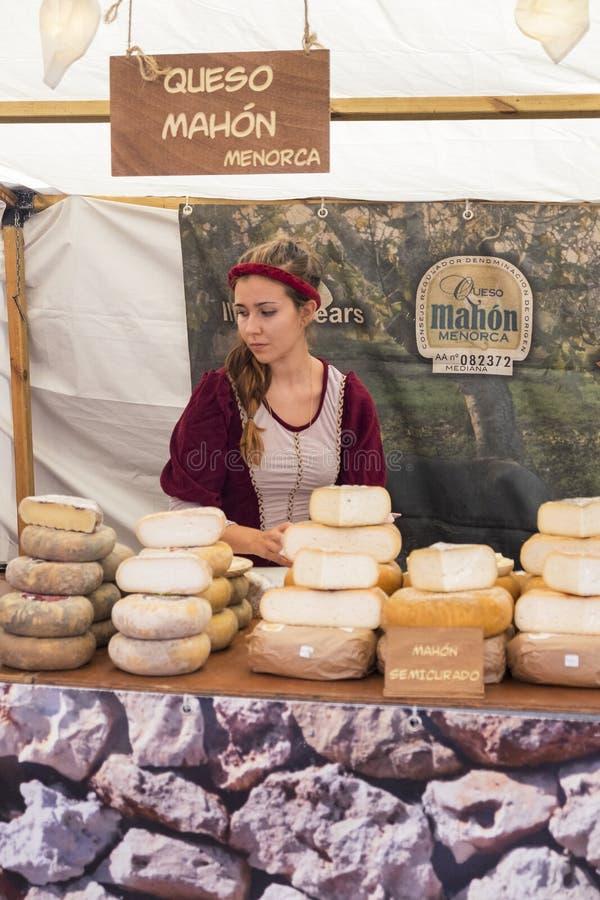 Kvinna som säljer ost i en medeltida marknad i Ã- vila arkivbild