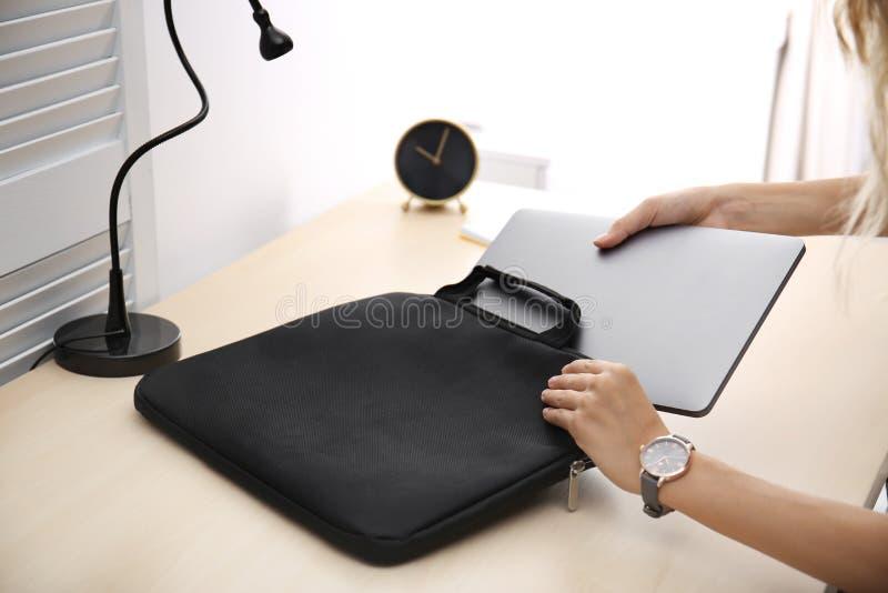 Kvinna som sätter bärbara datorn in i fall på tabellen arkivfoto