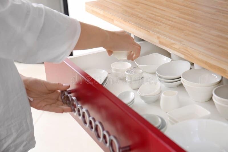 Kvinna som sätter bunken in i kökenhet fotografering för bildbyråer