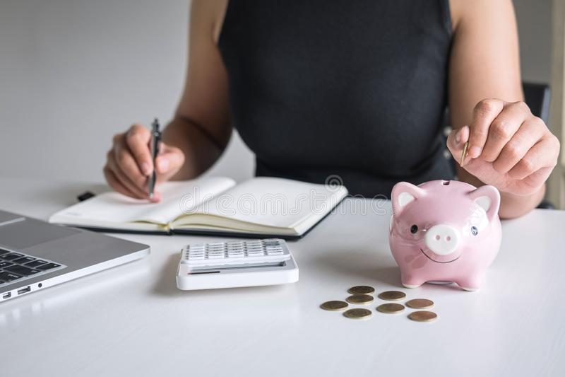 Kvinna som sätter det guld- myntet i den rosa spargrisen för moment upp växande affär till vinst och sparar med spargrisen, spara royaltyfri fotografi