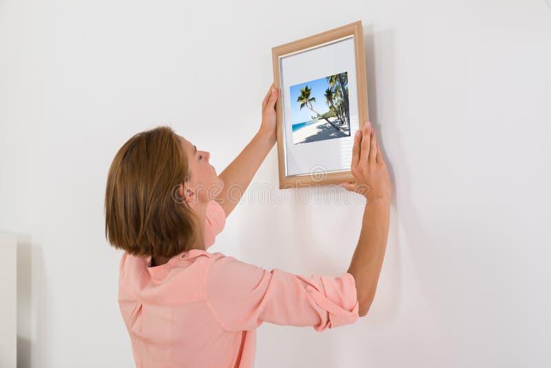 Kvinna som sätter fotoramen på väggen arkivfoto