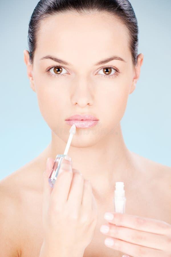 Kvinna som sätter läppstift på henne kanter arkivfoto