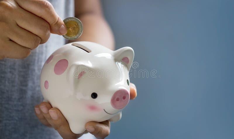 Kvinna som sätter myntet in i spargrisen för sparande royaltyfri fotografi