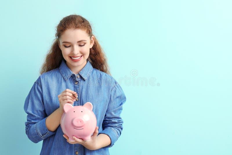 Kvinna som sätter myntet in i spargrisen på färgbakgrund besparingar f?r pengar f?r flaskbegreppsdollar arkivfoto