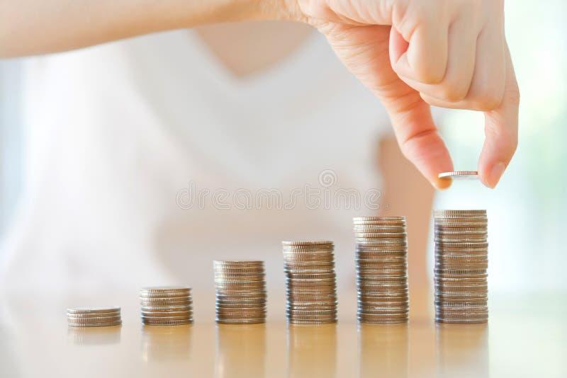 Kvinna som sätter myntet till den stigande bunten av mynt arkivbilder