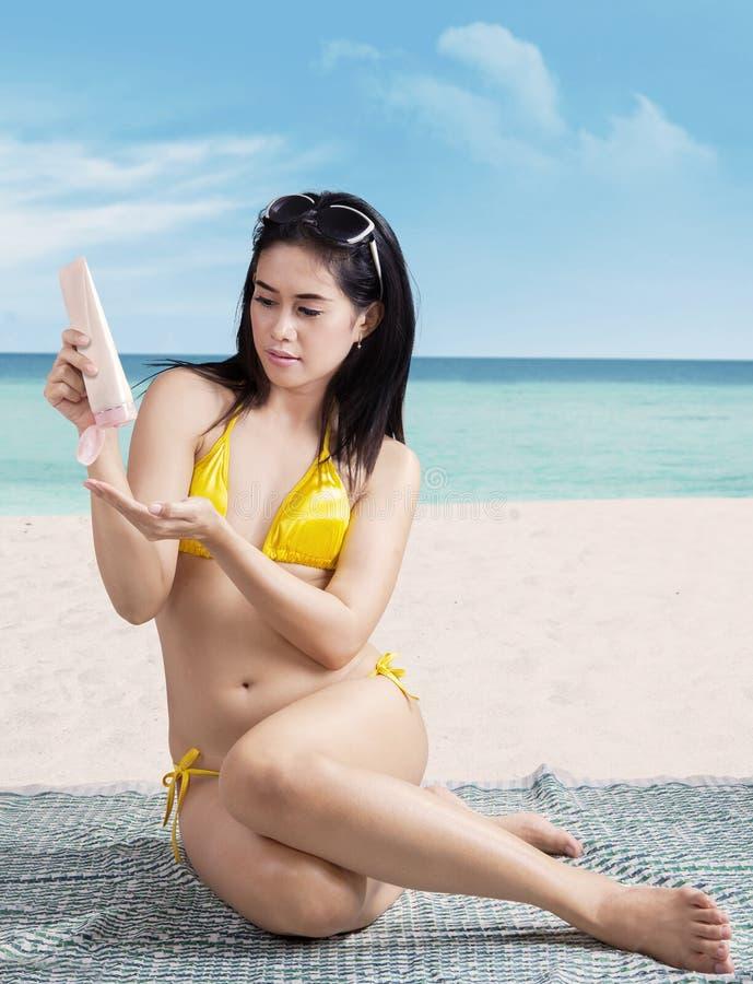 Kvinna som sätter på sunscreen royaltyfria bilder