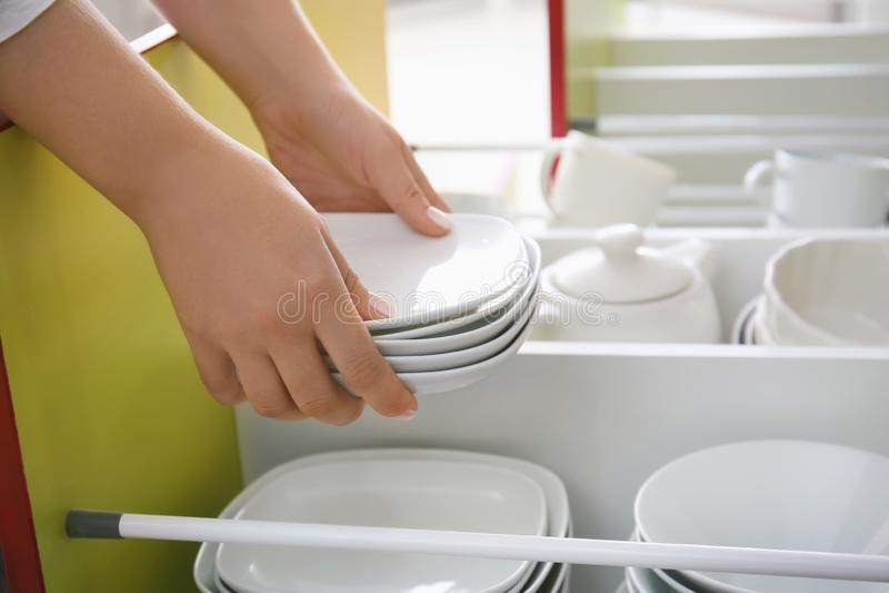 Kvinna som sätter plattor in i kökenhet fotografering för bildbyråer