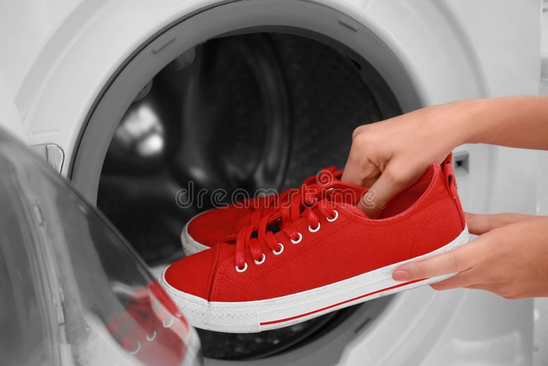 Kvinna som sätter röda gymnastikskor in i tvagningmaskinen arkivbild