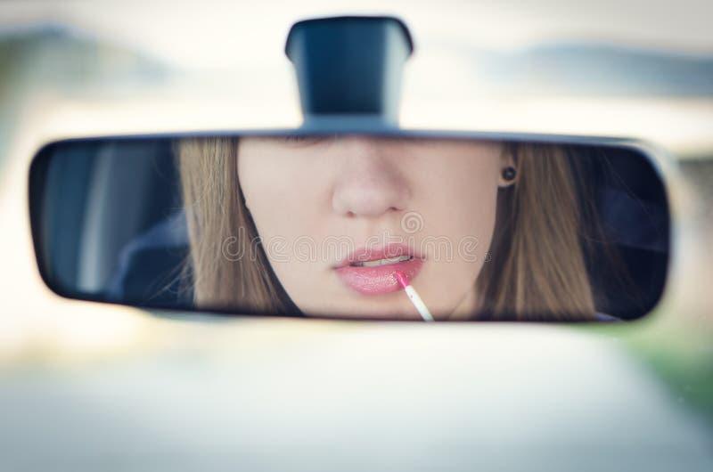 Kvinna som sätter smink i en bil Nätt ung kvinna som ser i spegel Farligt läge arkivfoton