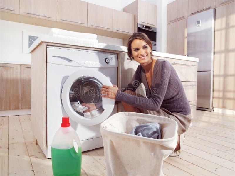 Kvinna som sätter torkduken in i tvagningmaskinen fotografering för bildbyråer