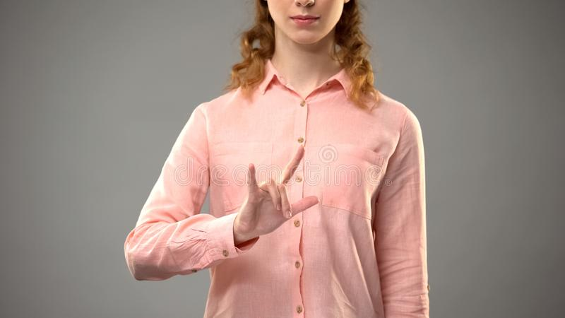 Kvinna som s?ger f?r?lskelse i teckenspr?ket som visar ord i asl-kurs, kommunikation royaltyfri foto
