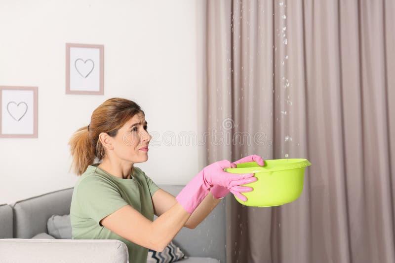 Kvinna som samlar läcka vatten från tak i vardagsrum royaltyfria foton