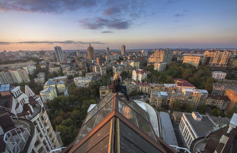 Kvinna som seatting på taket av modern byggnad i Kiev, Ukraina fotografering för bildbyråer
