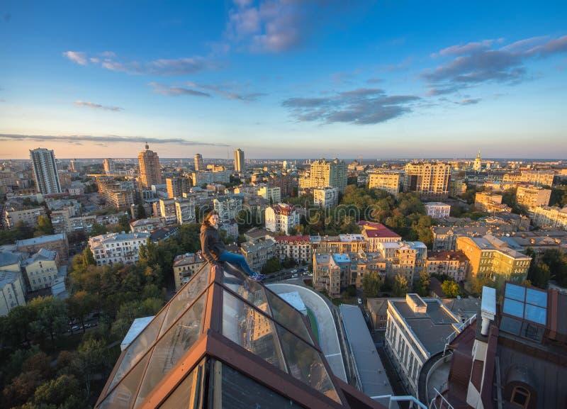 Kvinna som seatting på taket på den moderna byggnaden i Kiev, Ukraina arkivbilder
