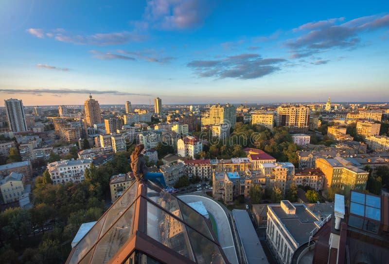 Kvinna som seatting på taket på den moderna byggnaden i Kiev, Ukraina royaltyfria bilder