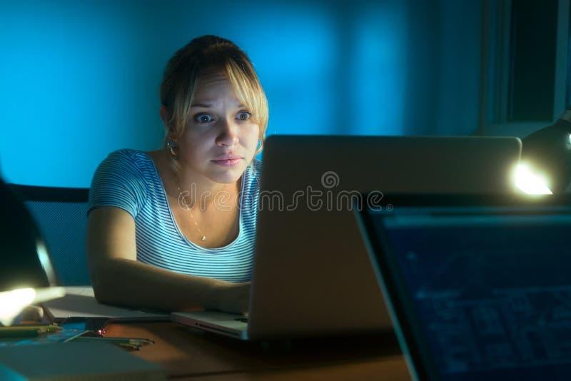 Kvinna som sent läser det läskiga meddelandet på social natt för nätverk - royaltyfri foto