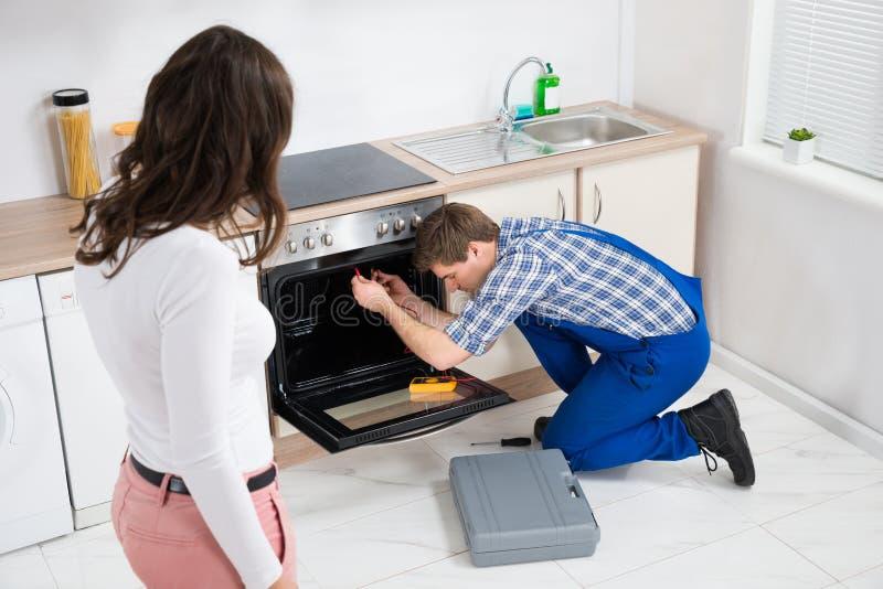 Kvinna som ser arbetaren som reparerar ugnen royaltyfri bild