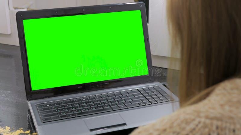 Kvinna som ser bärbara datorn med den gröna skärmen royaltyfri foto