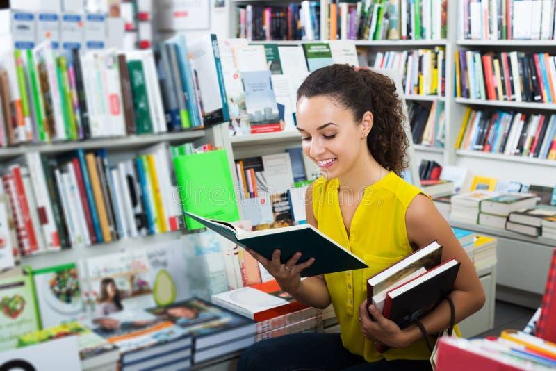 Kvinna som ser boken arkivfoto