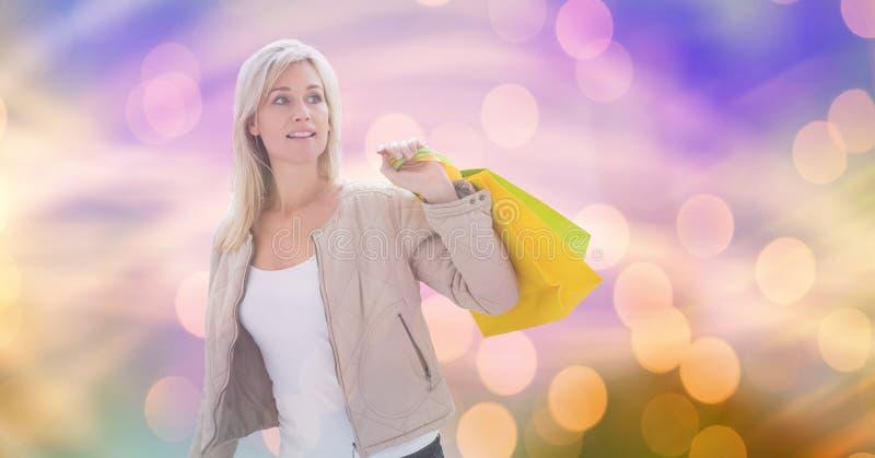 Kvinna som ser bort, medan bära shoppingpåsar över bokeh royaltyfri foto