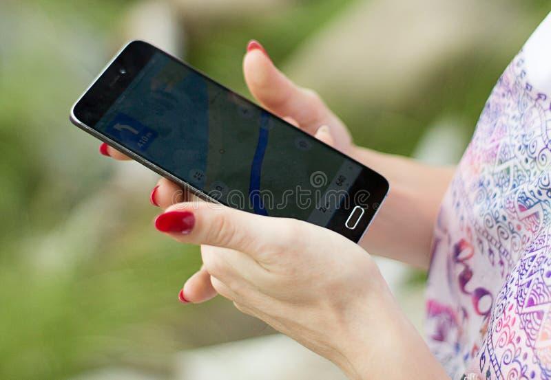 Kvinna som ser den bästa vägen till läge med navigatören i en telefon royaltyfria bilder