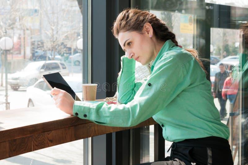 Kvinna som ser den digitala minnestavlan med den tomma skärmen i coffee shop royaltyfri foto