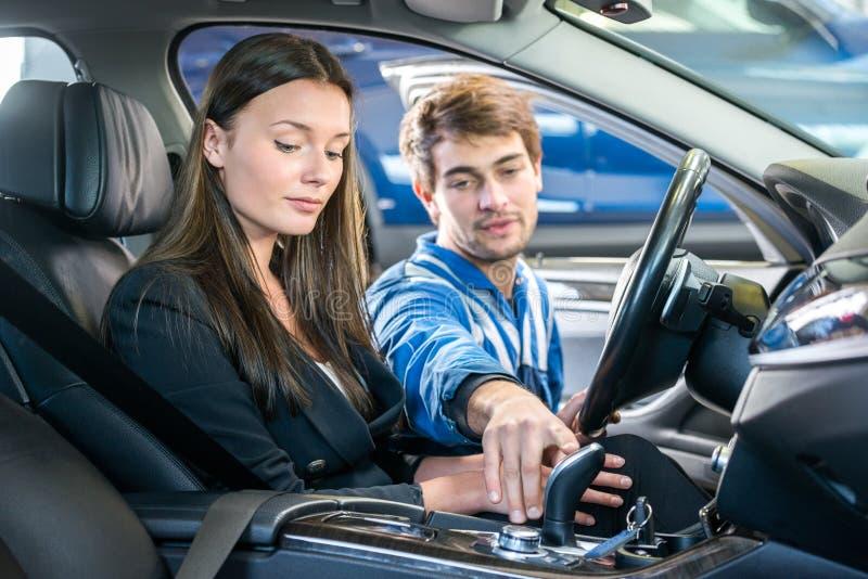 Kvinna som ser den mekanikerChecking Gearshift Of bilen arkivfoto