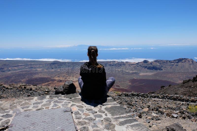 Kvinna som ser ett torrt och stenigt vulkaniskt landskap på Teide - Spanien arkivfoto