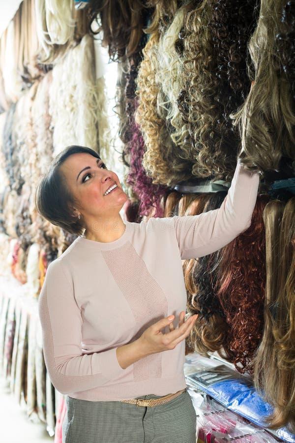 Kvinna som ser färghårförlängningar arkivfoto