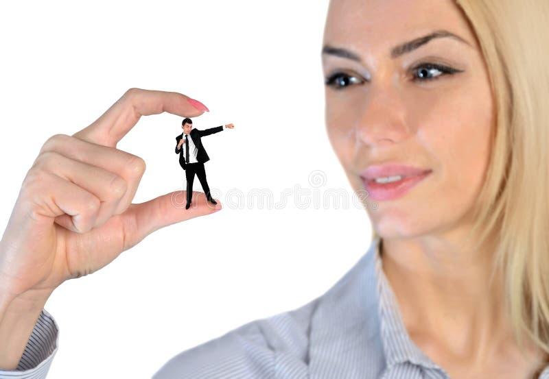 Kvinna som ser förbluffad på liten man arkivfoto