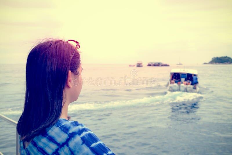 Kvinna som ser fartyget som seglade i väg från henne i tappningstil arkivbild
