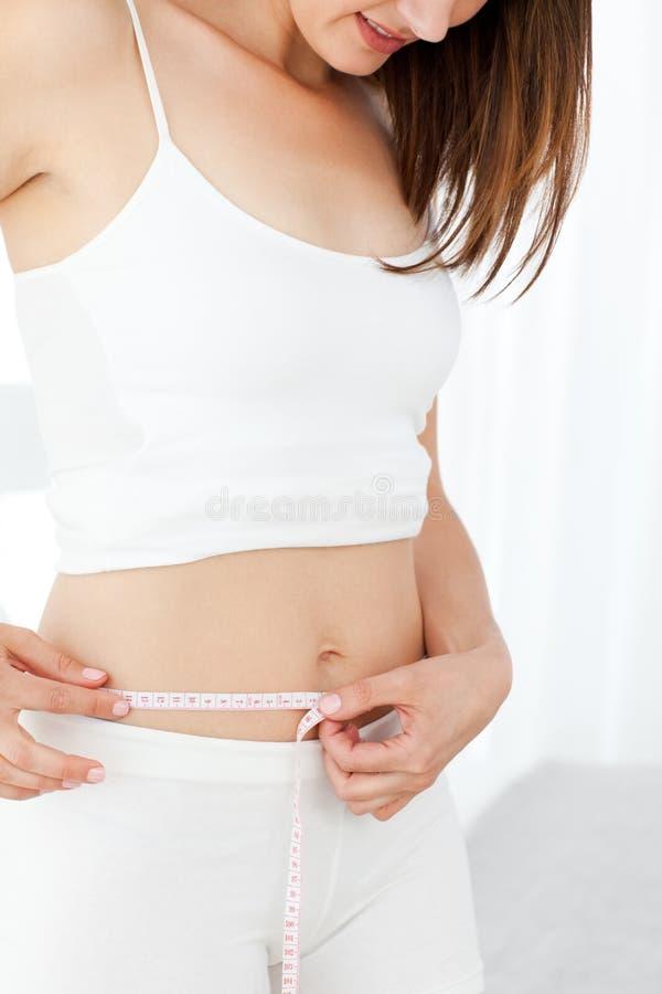 Kvinna som ser henne waistline arkivfoto