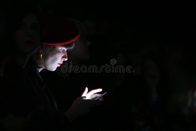 Kvinna som ser hennes smartphone arkivbilder