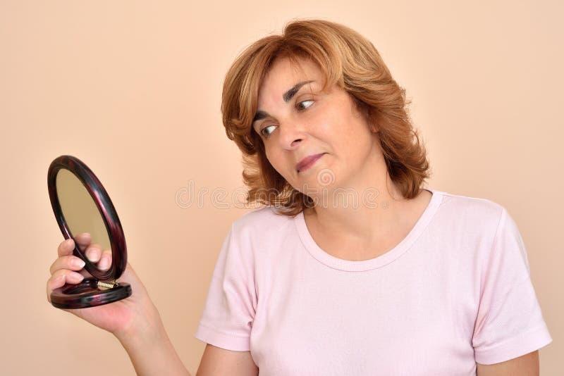 Kvinna som ser hennes smink och nya frisyr i spegeln fotografering för bildbyråer