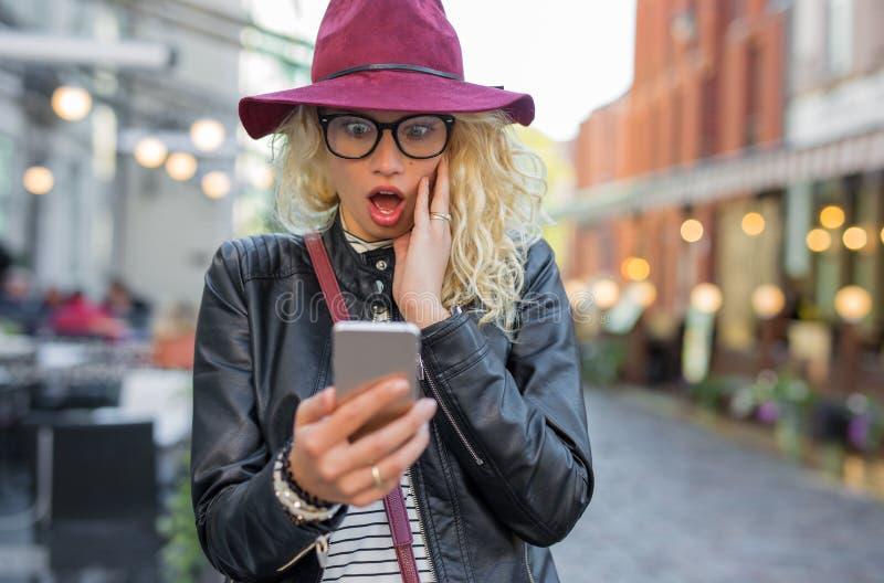 Kvinna som ser hennes telefon i chock fotografering för bildbyråer