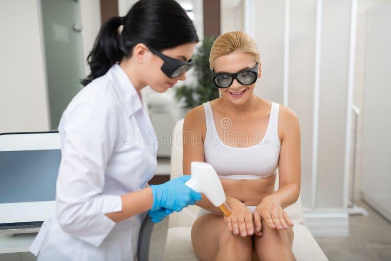 Kvinna som ser hur cosmetologist som gör hennes laser-tillvägagångssätt royaltyfri fotografi